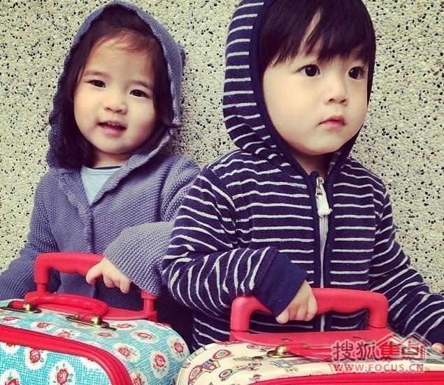 小女孩子拿着行李箱,小男孩也拿着.