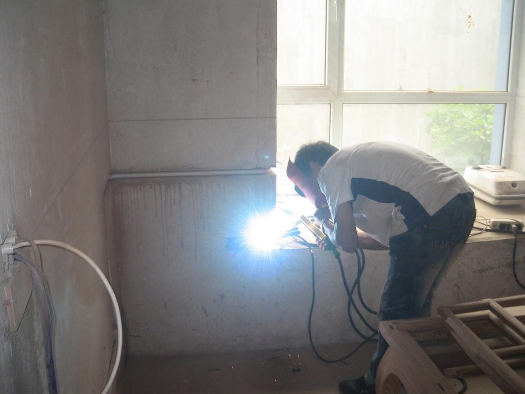 7.抠飘窗窗台板耳朵时,发现里面有几根钢筋。角磨够不着,就用电焊熔断!
