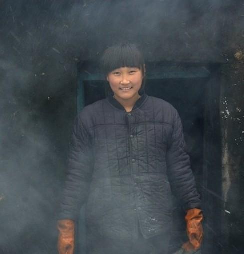 贾鑫在豆腐房搬运蜂窝煤准备烧火用.图片