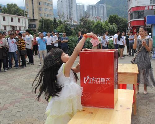 可爱的小女孩垫着脚尖把赈灾款投入了募捐箱