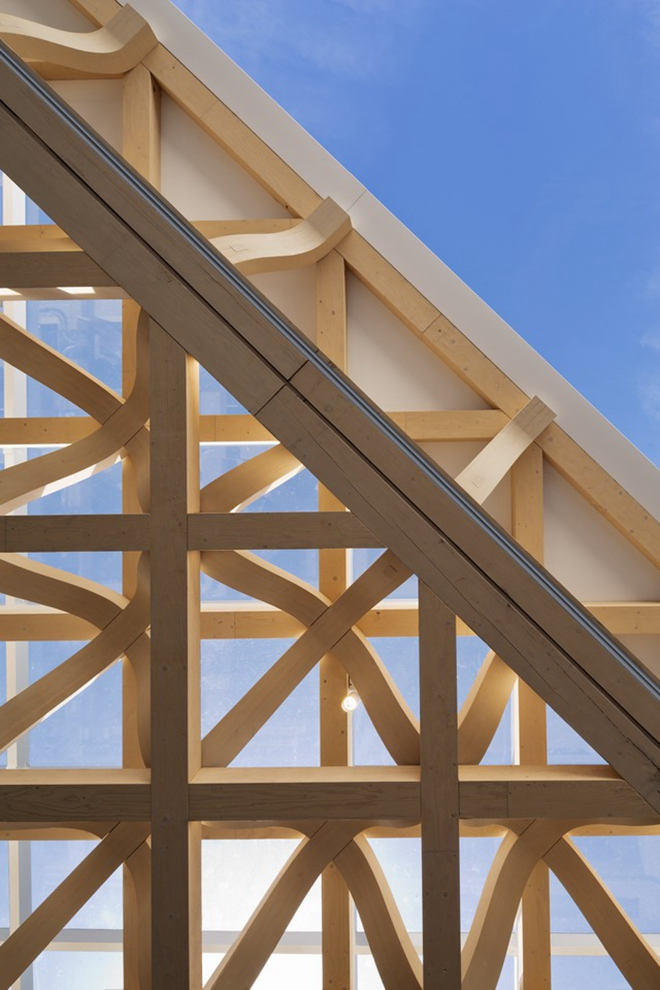 创新的三角形木屋顶桁架覆盖了整个内部空间以及屋顶露台的部分室外