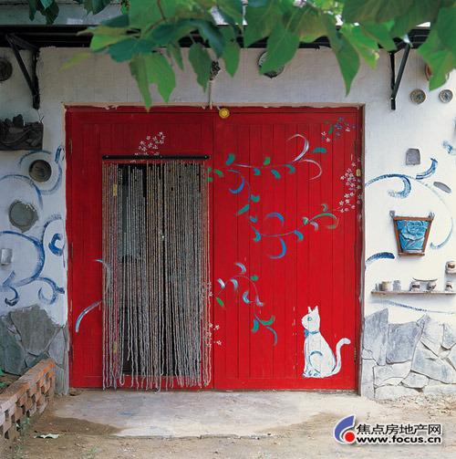 被漆成红色的大门,一只安静的小猫正静静看着童话之门的开启