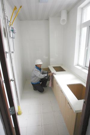 装修好的公租房内,装修工人正在做室内清洁.图片