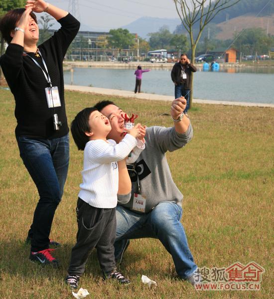 一家三口,享受在开阔草地上放风筝的乐趣图片