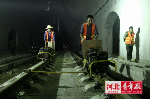 工人推着打丝机逐个拧紧固定螺丝(图片来源:河北青年报)