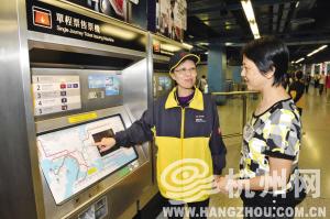 """香港地铁里,""""服务大使""""正在售票机前帮助乘客查询站点。(港铁公司提供)"""