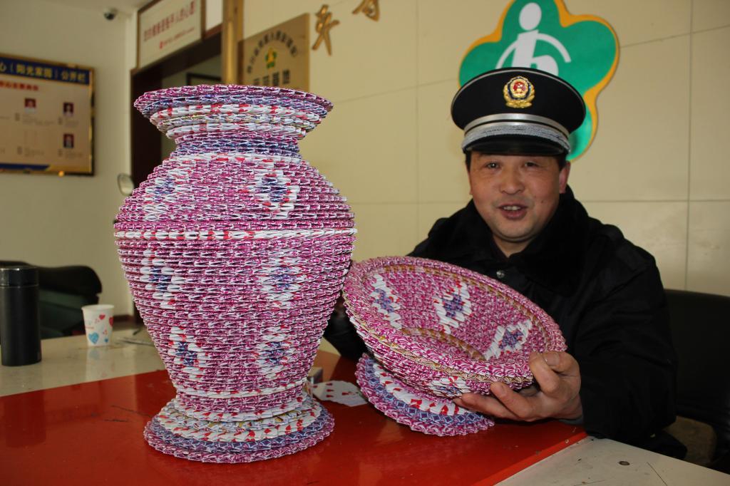 """李兴贵和他用扑克牌制作的""""花瓶""""与""""果盘""""."""